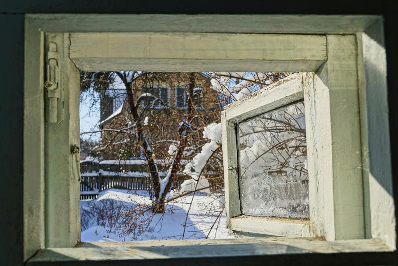Open window with a view of the winter street. Gray open window with a view of the sunny winter street royalty free stock photo