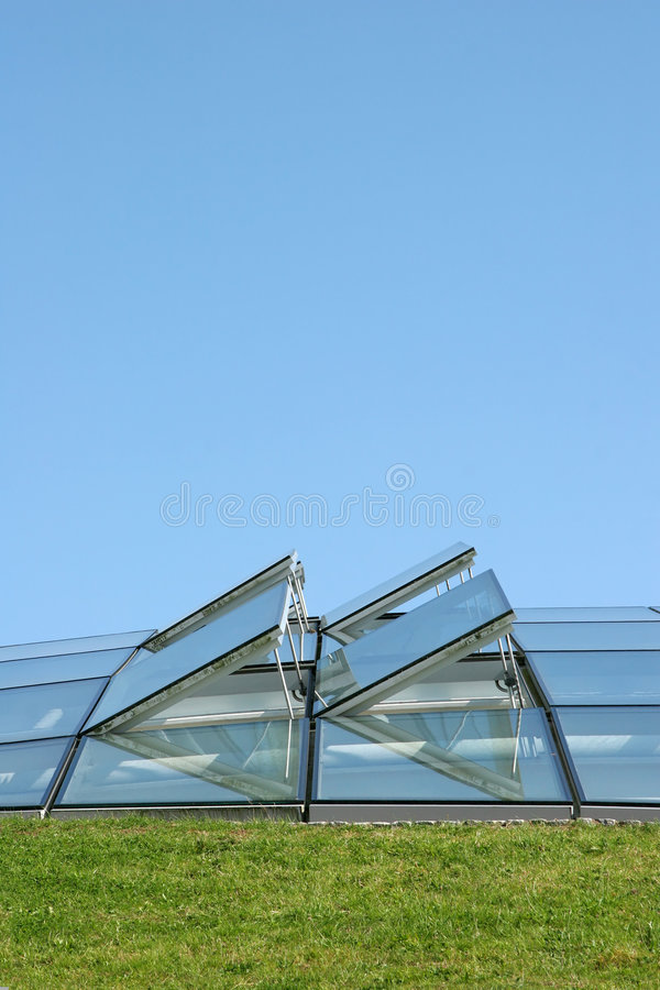 Open Windows. Open glass ventilation windows on a conservatory roof. Set against a blue sky with grass to the foreground royalty free stock photos