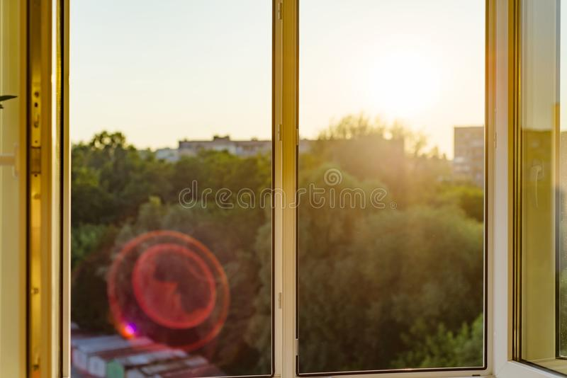 Open windows in the apartment. Background evening sunset, city silhouette royalty free stock photos