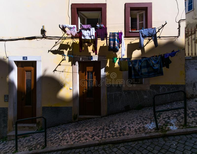 Open windows and linen. Ordinary stories of the old Lisbon. Portugal. As in Lisbon, clothes are dried. Simple life without a beauty. Paving stone on the royalty free stock image