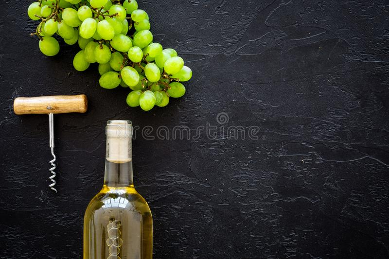 Open the wine concept. White wine in glass bottle near bunch of grapes and corkscrew on black background top view copy stock photos
