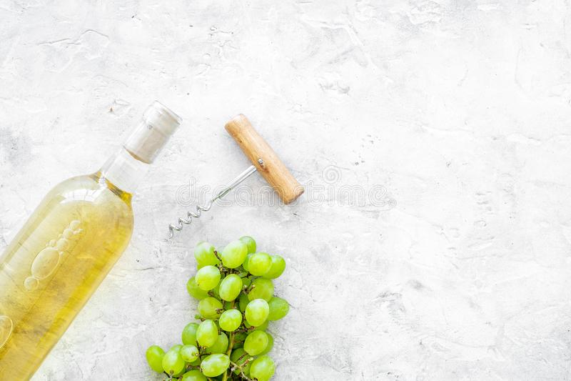 Open the wine concept. White wine in glass bottle near bunch of grapes and corkscrew on grey background top view copy. Open the wine concept. White wine in glass royalty free stock photos