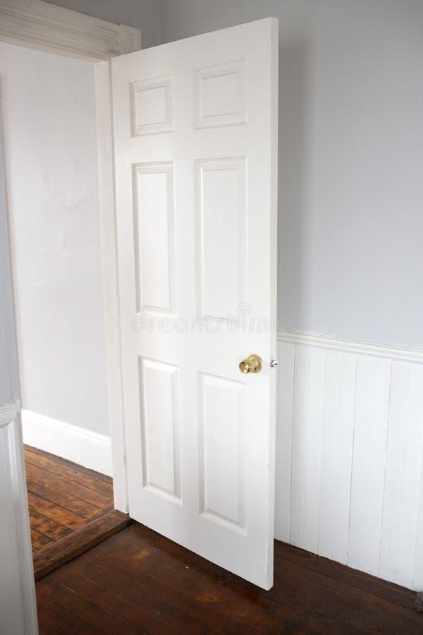 Open witte deuropening met houten vloeren stock afbeeldingen