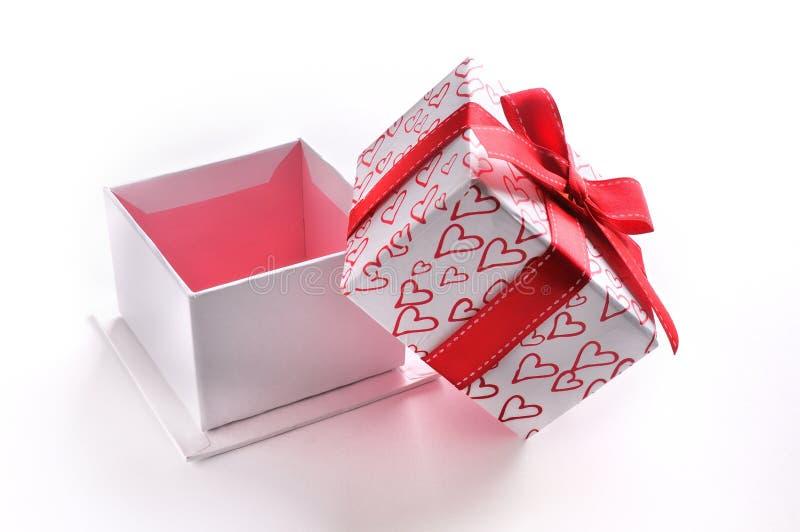 Open witte giftdoos met geïsoleerde boog en geschilderde harten royalty-vrije stock foto's