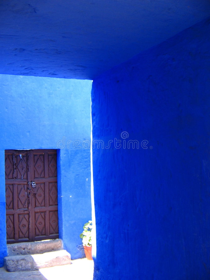 Open Wooden Door in Blue Wall. Open wooden door going into street against blue walls, arequipa, peru stock image