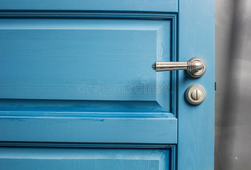 Open wooden door painted in blue color. Open wooden door painted in blue with a beautiful a metal handle and the castle stock photography
