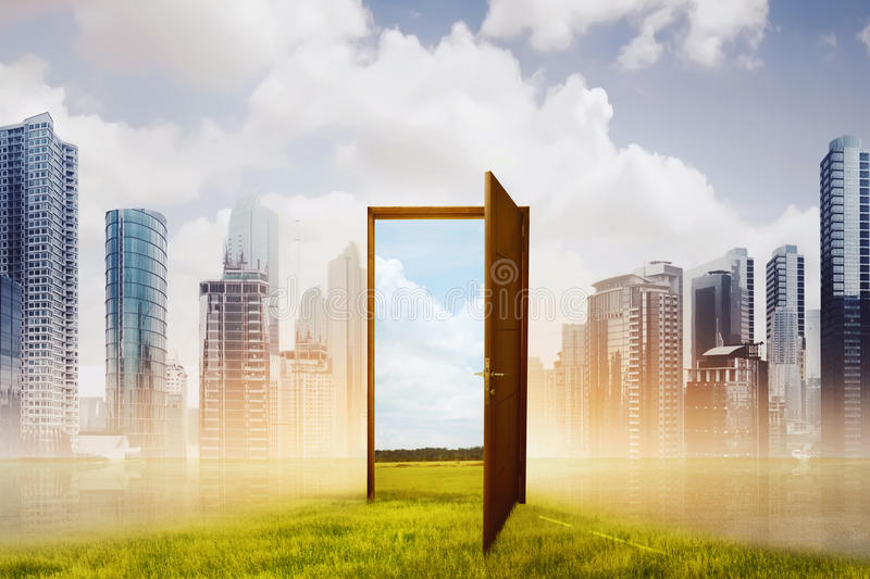 Open wooden door to the new world with green meadow royalty free stock image