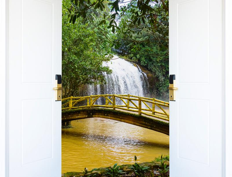 Open wooden door waterfall royalty free stock image
