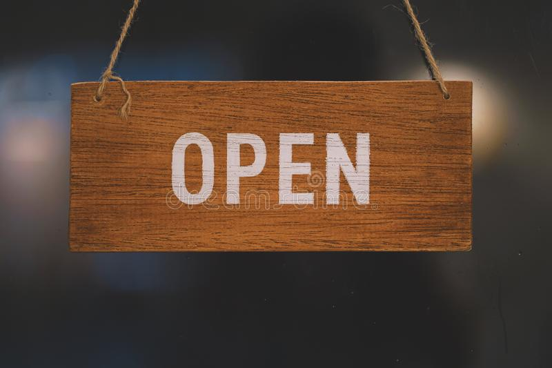 Open wooden sign broad through the glass of door in cafe. stock photography