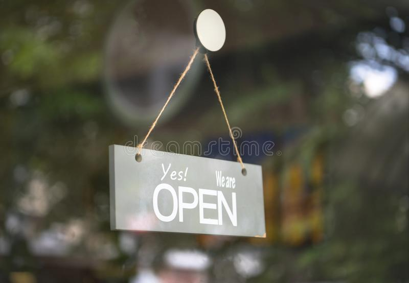 Open wooden sign hanging the glass of coffee shop door stock photography