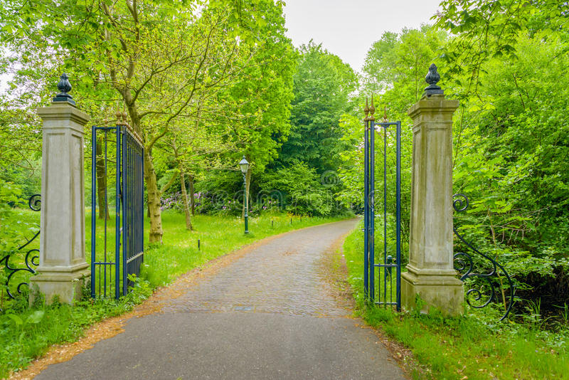 Open wrought iron gate between two stone pillars stock images