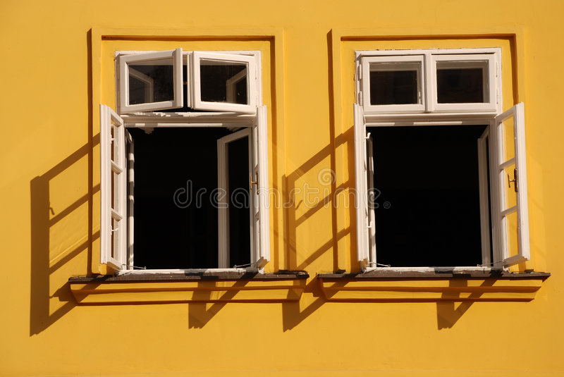 Open your mind. Two windows wide open with a yellow wall in a background royalty free stock photography