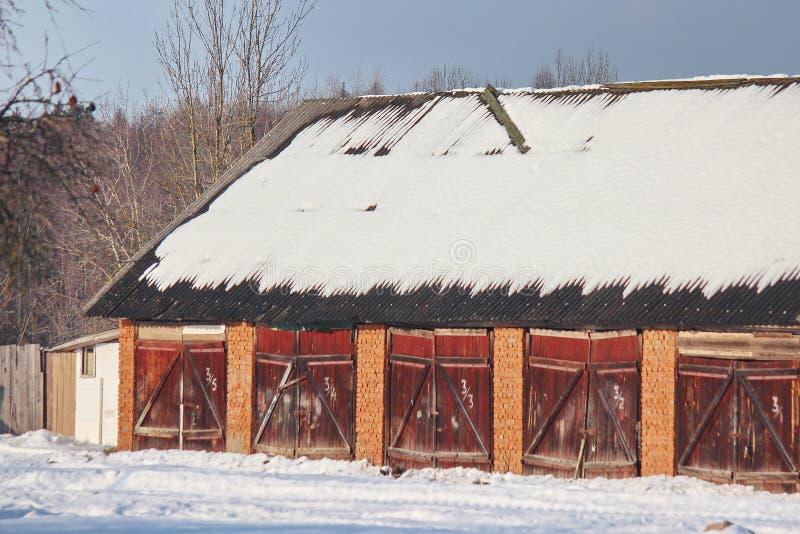 Openbare dorpsgarages of loodsen in de winter op een Zonnige dag De sneeuw op het dak is genummerd ingangen royalty-vrije stock afbeelding