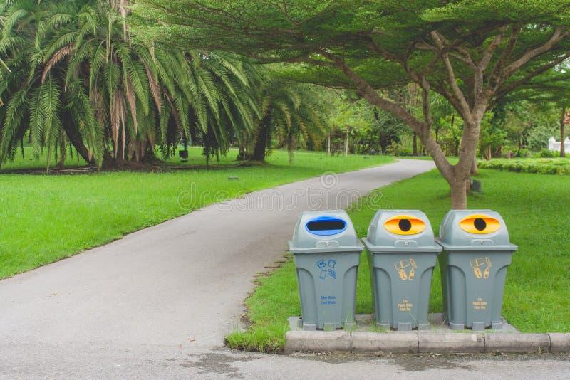 Openbare kringloopbakken of afgezonderde afvalbakken die op concrete vloer naast gang in openbaar park zitten stock foto's