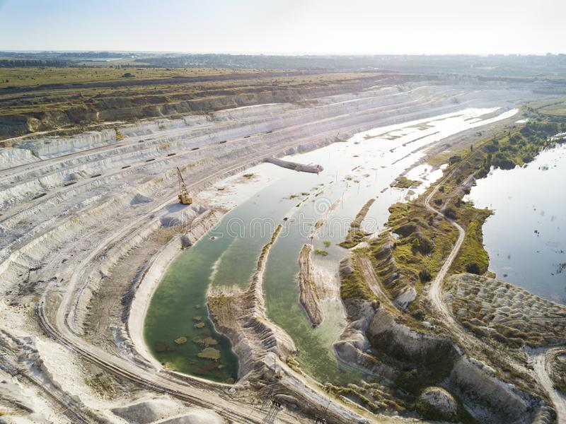 Opencast mining quarry with machinery at work - Aerial view. Industrial Extraction of lime, chalk, calx, caol. View from above.  royalty free stock photo