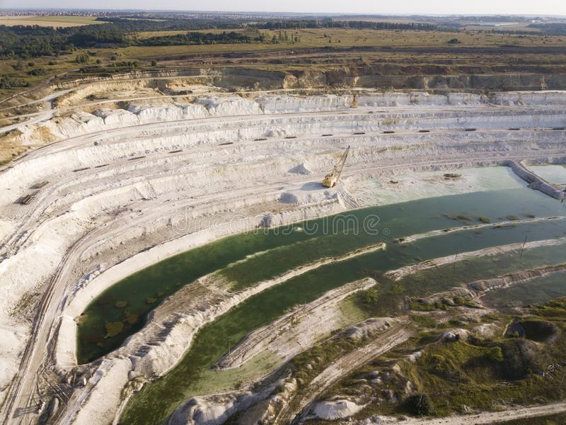 Opencast mining quarry with machinery at work - Aerial view. Industrial Extraction of lime, chalk, calx, caol. View from above.  royalty free stock photos