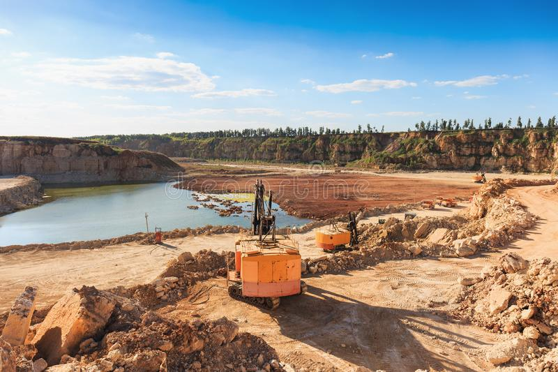 Opencast sand mining quarry with excavator and other machinery at work, industrial production of pit, gravel, minerals and ore. Toned royalty free stock image