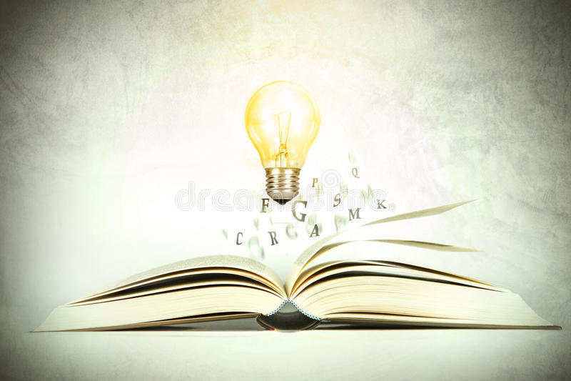 The opened book with alphabet letter flying out with glowing light bulb of pages , education and knowledge concept, vintage color royalty free stock photo