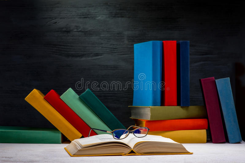 Opened book with glasses and another colorful books stock image