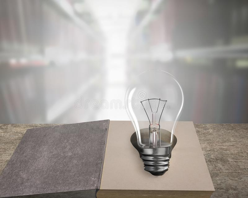 Opened book with light bulb on wooden table royalty free stock image