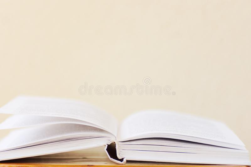 Opened book lying on wooden table blank white wall background. College school university education learning literacy royalty free stock photo