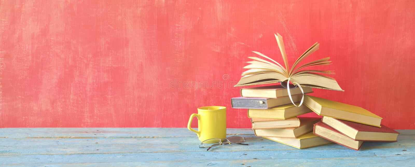 Opened Book on a pile of old books and a cup of coffee and specs. Panorama, good copy space royalty free stock images