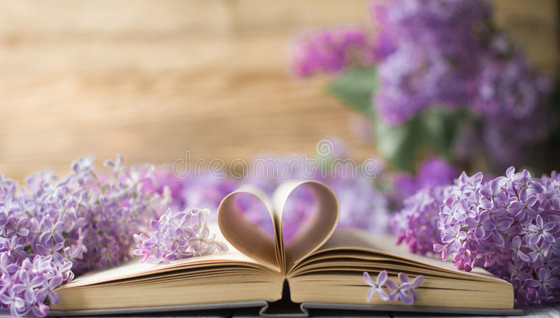 Opened book on the table with pages like heart and flowers royalty free stock image