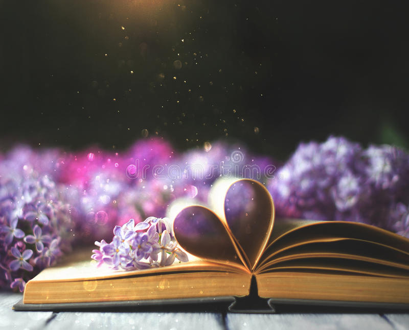 Opened book on the table with pages like heart and flowers stock photo