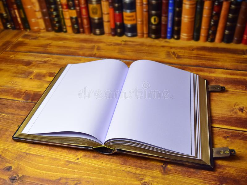 Opened book on the wooden table with leather books in the background royalty free stock image