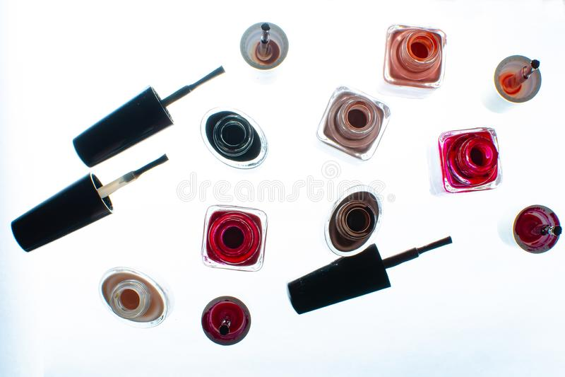 Opened bottles with nail polish on a white surface. stock image