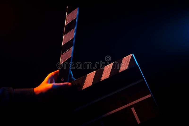 Opened clapperboard for cinema in hand, before filming on a black isolated background. With red and blue backlighting royalty free stock photography