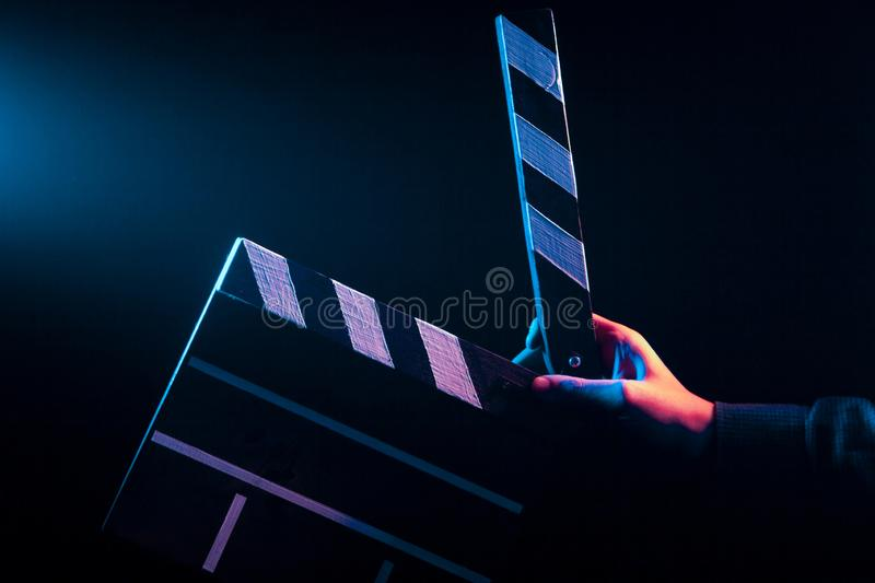Opened clapperboard for cinema in hand. Before filming on a black isolated background with red and blue backlighting royalty free stock photo