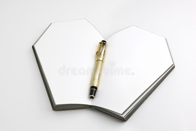 Opened coffin shaped book lay down to the table isolated and with the gold pen between pages stock photo