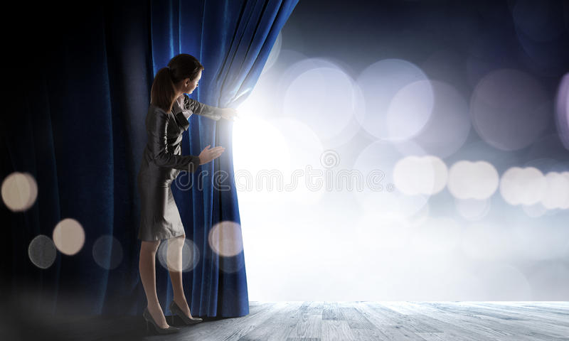 Opened curtain. Young businesswoman opening stage curtain to another reality royalty free stock image