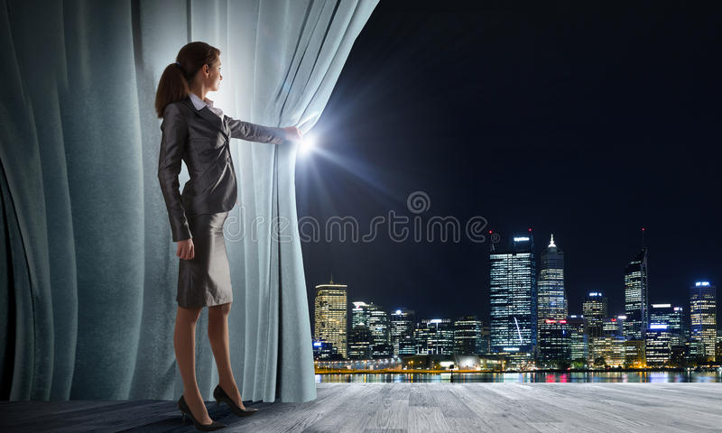 Opened curtain. Young businesswoman opening stage curtain to another reality royalty free stock photo