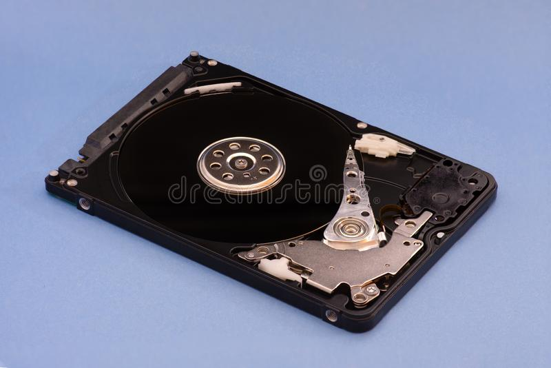 Opened disassembled hard drive from the computer, hdd with mirror effect. on blue background royalty free stock photography