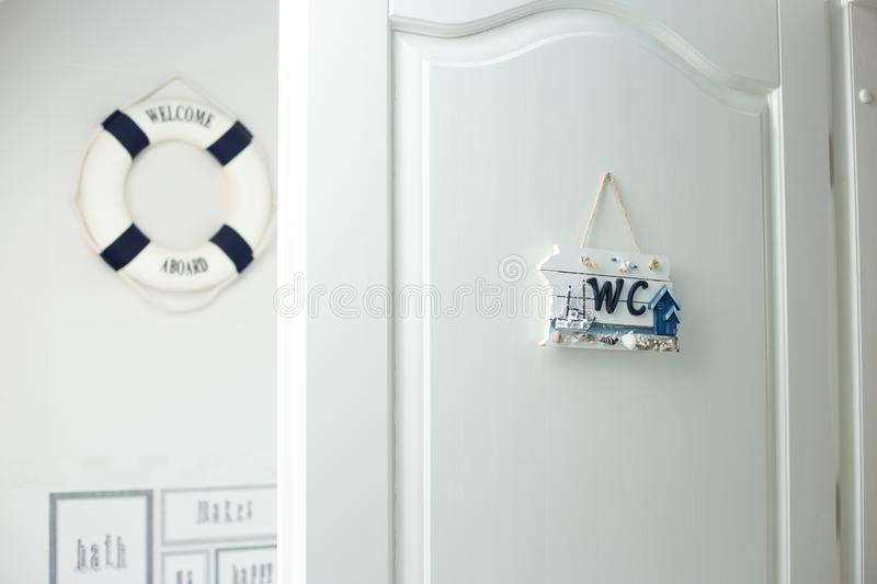 White bathroom and wc with sign on the door. Opened door of wc and bathroom in white color marina style  nobody simple concept stock photo