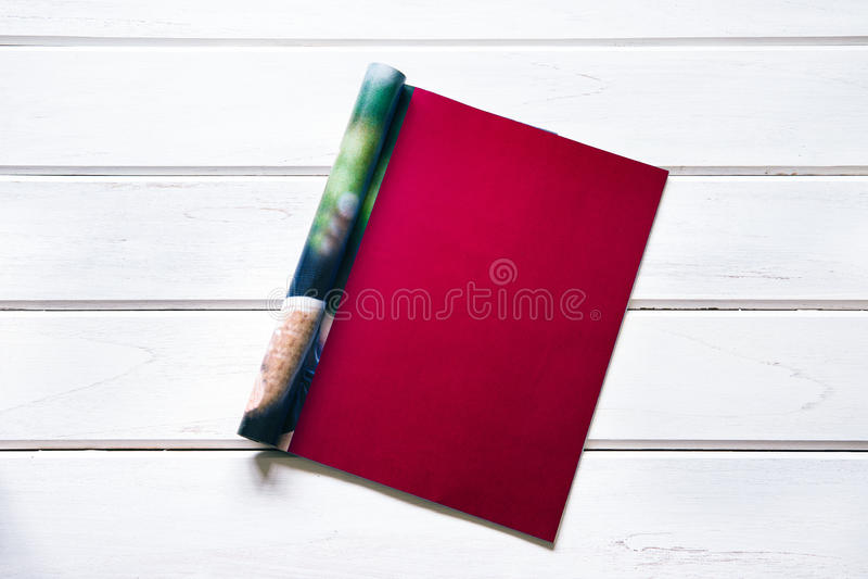 Opened the empty dark red mock up magazine page on white wooden. Opened empty dark red mock up magazine page on white wooden table background royalty free stock photos