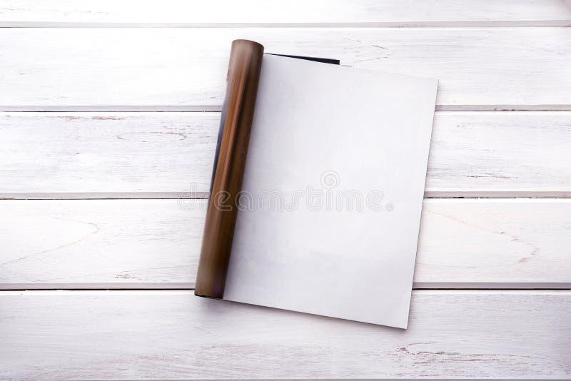 The Opened empty white mock up magazine page on white wooden tab. Opened empty white mock up magazine page on white wooden table background royalty free stock photo