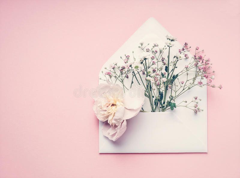Opened envelop with flowers arrangement on pastel pink background, top view, copy space. Creative greeting, Invitation royalty free stock photography