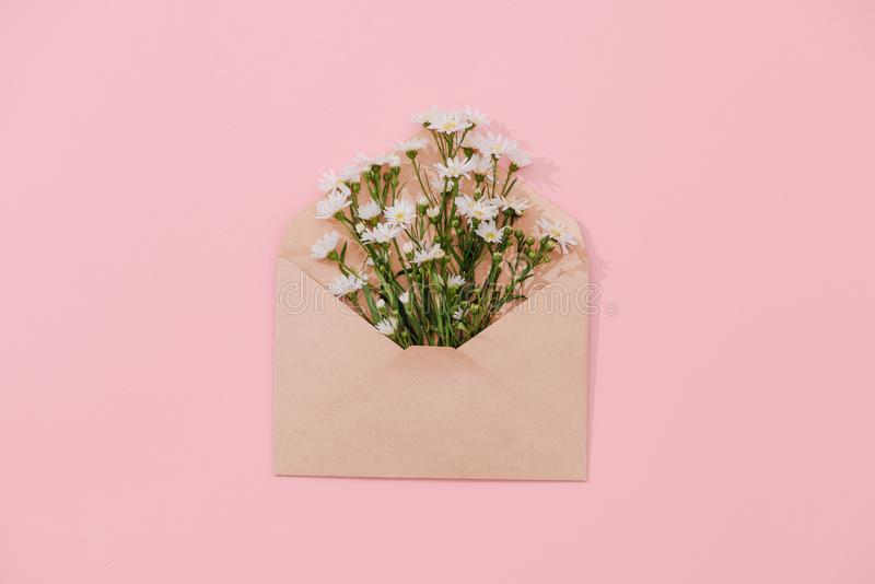 Opened envelope with flowers arrangements on pink background, to. P view. Festive greeting concept royalty free stock image
