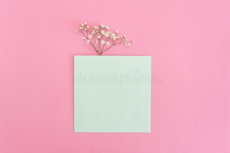 Opened envelope with Peonies flowers arrangements on pink background, top view. Festive greeting concept.  stock photography