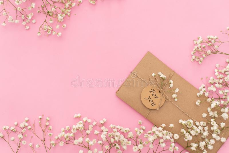 Opened envelope with Peonies flowers arrangements on pink background, top view. Festive greeting concept.  stock images