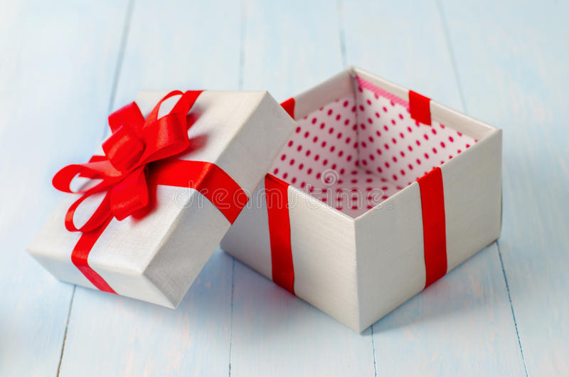 Opened gift box with red ribbon stock photos