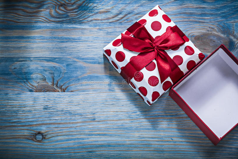 Opened gift box with red ribbon on wooden board holidays concept stock photos