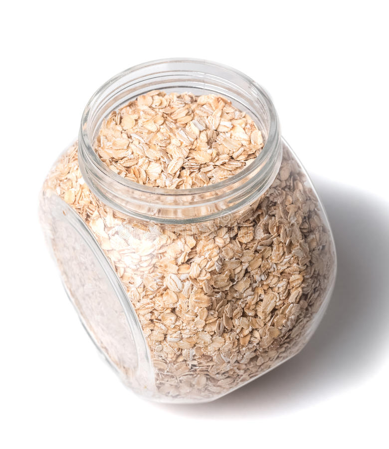 Opened glass jar with rolled oats isolated on white background glass jar with oatmeal flakes isolated stock photo