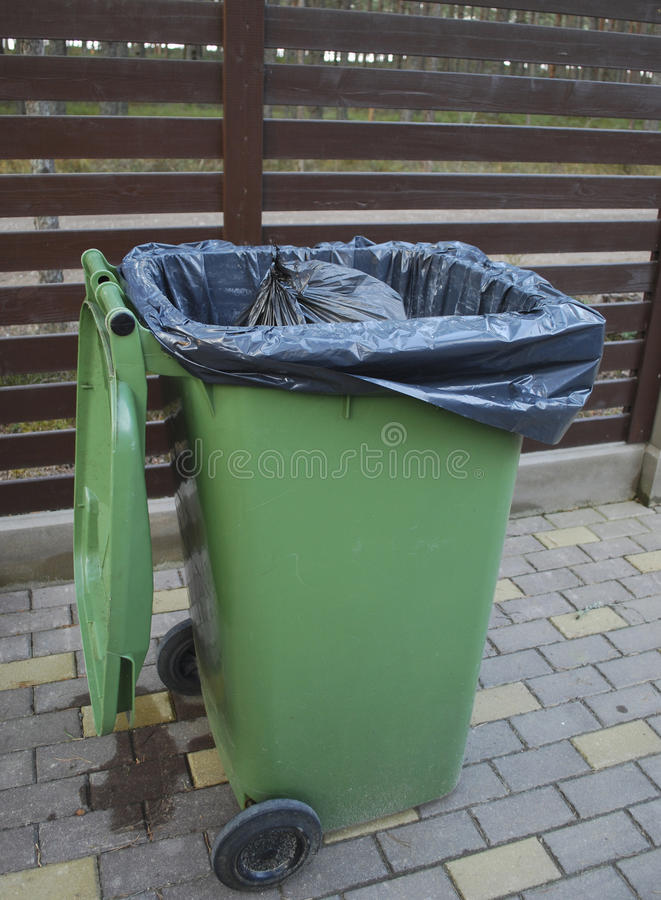 Opened green dumpster on brown wooden fence background. Black bag of trash with strings is inside dumpster royalty free stock photos