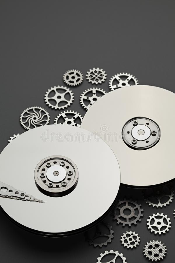 Opened hard disk drive and small gears on gray background stock photography