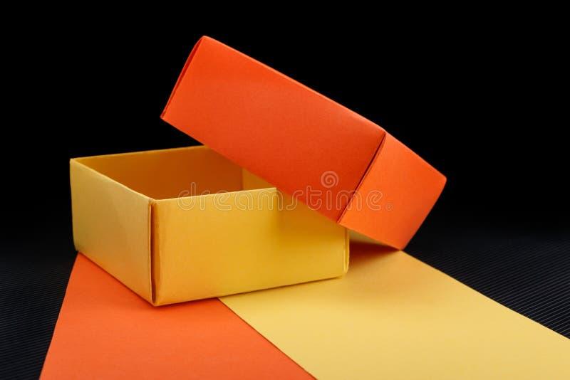 Opened homemade paper gift box on dark background. Opened homemade yellow and orange paper gift box on dark background stock image