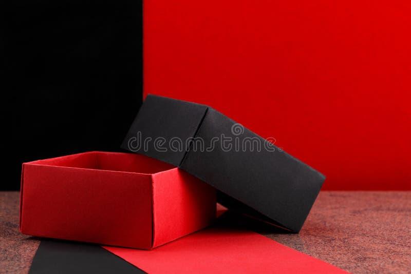 Opened homemade paper gift box on granite surface. Opened homemade black and red paper gift box on granite surface stock photo
